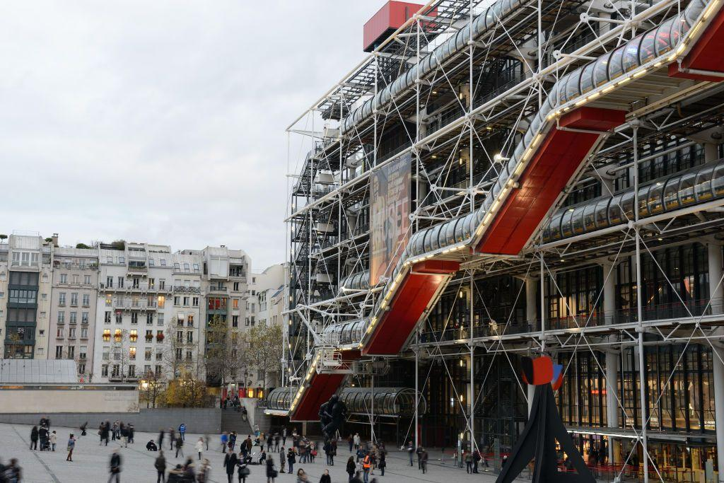 """<p>President Georges Pompidou commissioned the revolutionary <a href=""""https://www.centrepompidou.fr/en"""" target=""""_blank"""">Centre Pompidou</a> in 1969 as the contemporary art capital of Paris. Designed by award-winning architects <a href=""""http://www.rpbw.com/"""" target=""""_blank"""">Renzo Piano</a> and <a href=""""https://www.rsh-p.com/"""" target=""""_blank"""">Richard Rogers</a>, the center boasts an inside-out style with color-coded pipes, air vents, and cables forming the facade, allowing the interiors to feel more open. Today, visitors can explore the many offerings of the complex including the largest museum for modern art in Europe, a public reading library,  and a music and acoustic research center.</p><p><a class=""""body-btn-link"""" href=""""https://www.centrepompidou.fr/en/Visit/Practical-information"""" target=""""_blank"""">Plan Your Visit</a></p>"""