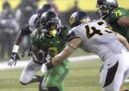 Oregon running back Byron Marshall, left, tries to evade California defender Dan Camporeale during the first half of an NCAA college football game in Eugene, Ore., Saturday, Sept. 28, 2013. (AP Photo/Don Ryan)