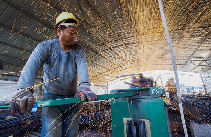 Labourer cuts steel bars at a railway bridge construction site in Lianyungang