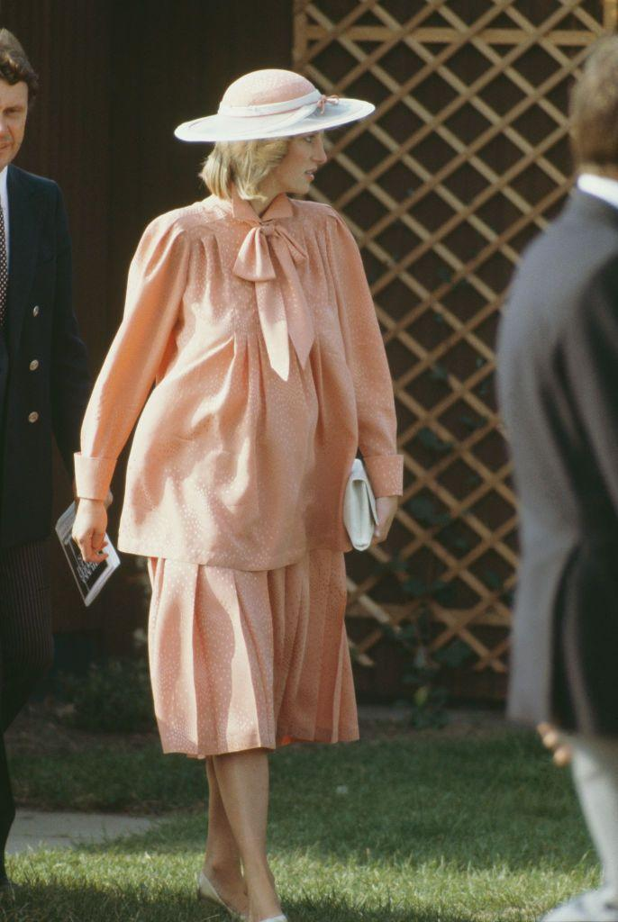<p>Princess Diana embraces the '80s maternity style of blousy silhouettes (and bows), with a monochromatic peach ensemble of billowing separates. </p>