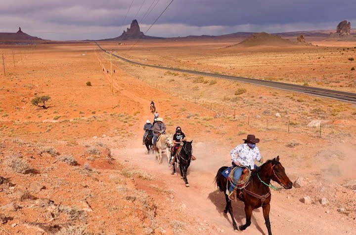 Allie Young, second in line, a Diné woman on the Navajo Nation in Arizona, is among a group of Native Americans as they ride on horseback to the polls on Election Day in Kayenta, Ariz., Tuesday, Nov. 3, 2020. (Larry Price via AP)