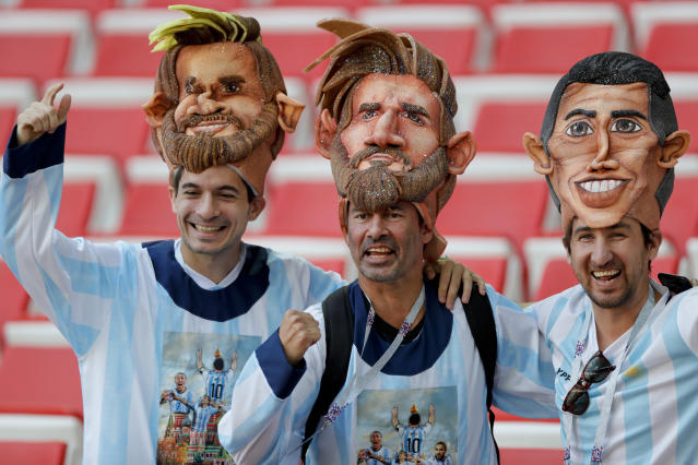 Argentina's fans wear masks of their team players Lionel Messi, left and center, and Angel Di Maria, right, as they get ready to cheer on their side before the start of the group D match between Argentina and Iceland at the 2018 soccer World Cup in the Spartak Stadium in Moscow, Russia, Saturday, June 16, 2018. (AP Photo/Ricardo Mazalan)