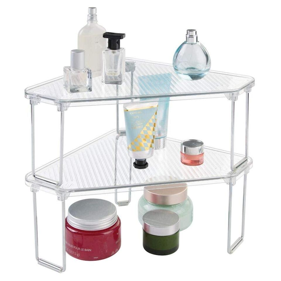 "<p>Get the most of your space by using this <a href=""https://www.popsugar.com/buy/mDesign-Corner-Stackable-Organizer-Shelf-551632?p_name=mDesign%20Corner%20Stackable%20Organizer%20Shelf&retailer=amazon.com&pid=551632&price=18&evar1=casa%3Aus&evar9=47251564&evar98=https%3A%2F%2Fwww.popsugar.com%2Fhome%2Fphoto-gallery%2F47251564%2Fimage%2F47252510%2FmDesign-Corner-Stackable-Organizer-Shelf&list1=cleaning%2Corganization%2Cspring%20cleaning%2Csmall%20space%20living%2Cbathrooms%2Chome%20organization&prop13=mobile&pdata=1"" class=""link rapid-noclick-resp"" rel=""nofollow noopener"" target=""_blank"" data-ylk=""slk:mDesign Corner Stackable Organizer Shelf"">mDesign Corner Stackable Organizer Shelf</a> ($18).</p>"