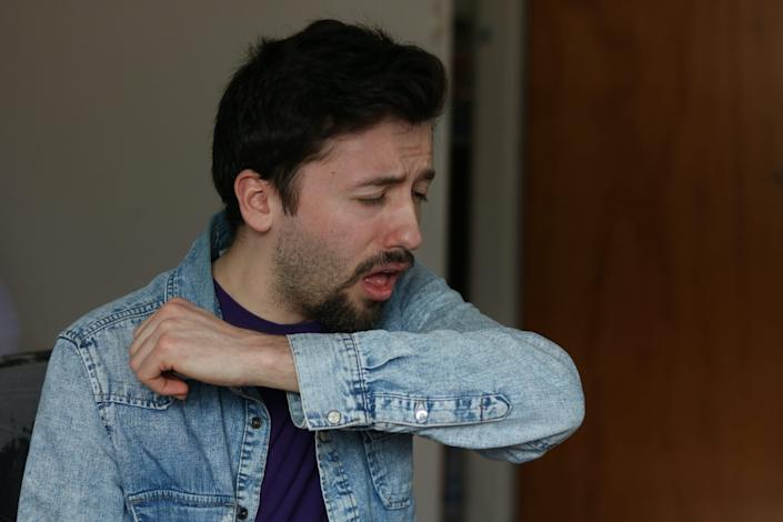 A man coughing into his elbow.