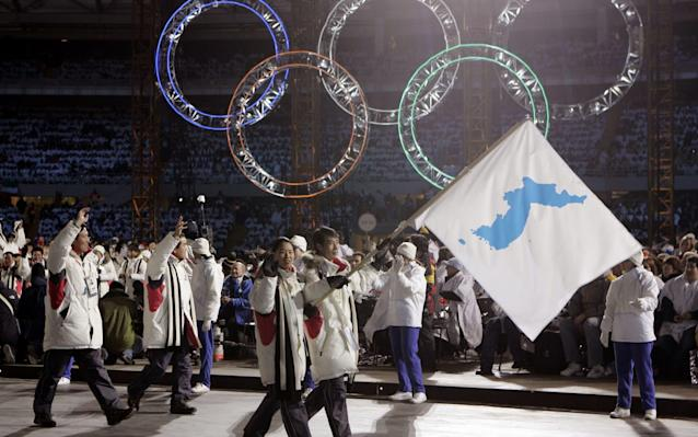 Korea flag-bearer's Bora Lee and Jong-In Lee, carrying a unification flag lead their teams into the stadium during the 2006 Winter Olympics opening ceremony in Turin, Italy, 2006 - AP