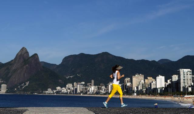 A woman runs near the Arpoador beach in Rio de Janeiro March 11, 2014. Rio de Janeiro is one of the host cities for the 2014 soccer World Cup in Brazil. REUTERS/Sergio Moraes (BRAZIL - Tags: SPORT SOCCER WORLD CUP)