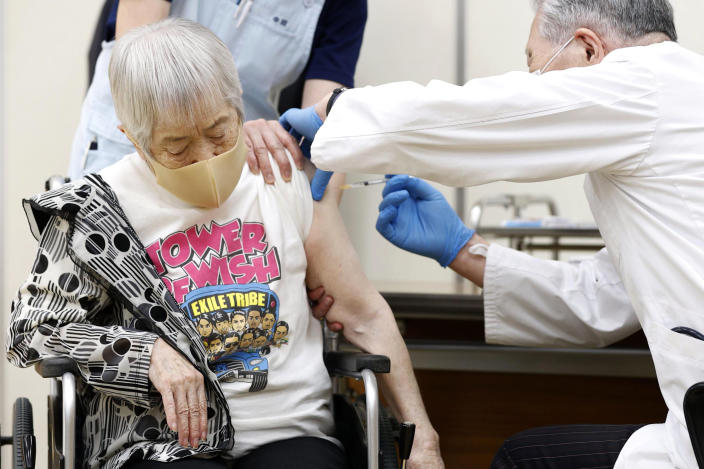 An elderly woman receives her first dose of Pfizer's COVID-19 vaccine at a special nursing home in Itami, Hyogo prefecture, western Japan, Monday, April 12, 2021. Japan started its vaccination drive with medical workers and expanded Monday to older residents, with the first shots being given in about 120 selected places around the country. (Kyodo News via AP)