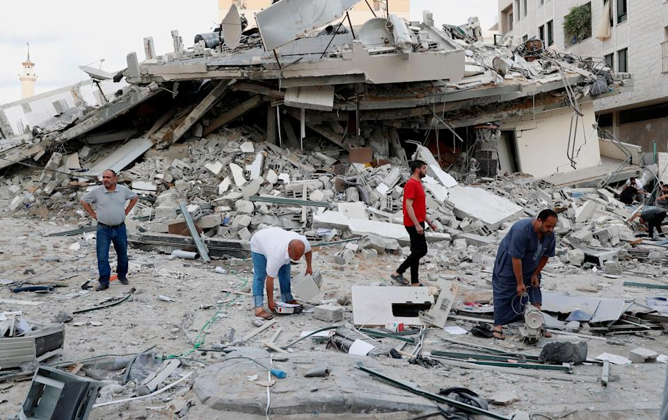 <p>People inspect the rubble of destroyed residential building that was hit by an Israeli airstrike, in Gaza City, Monday, May 17, 2021</p> (AP Photo/Adel Hana)
