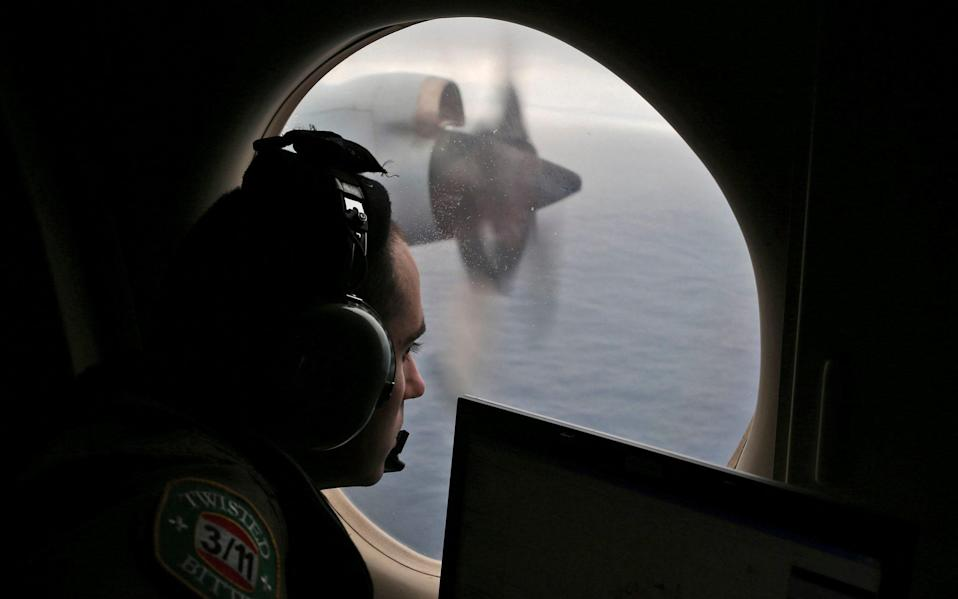 Flight officer Rayan Gharazeddine scans the water in the southern Indian Ocean for MH370 - AP Photo/Rob Griffith