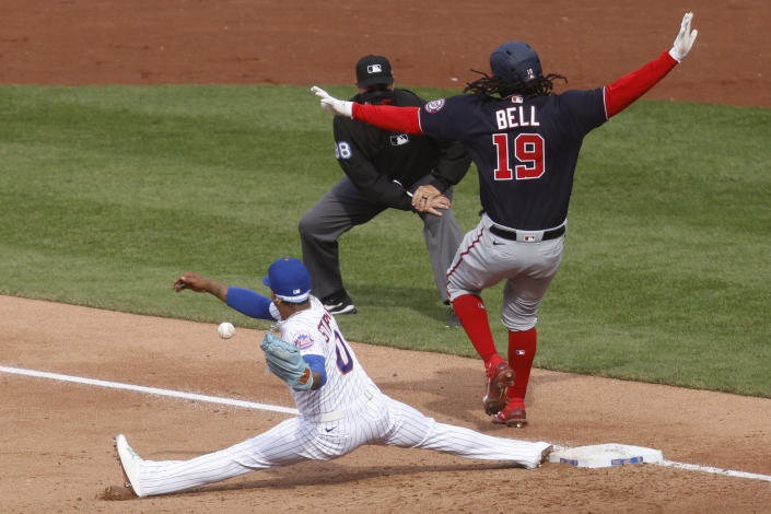 Washington Nationals' Josh Bell (19) is safe at first after a missed catch by New York Mets' Marcus Stroman, left, during the third inning of a baseball game, Saturday, April 24, 2021, in New York. (AP Photo/Jason DeCrow)