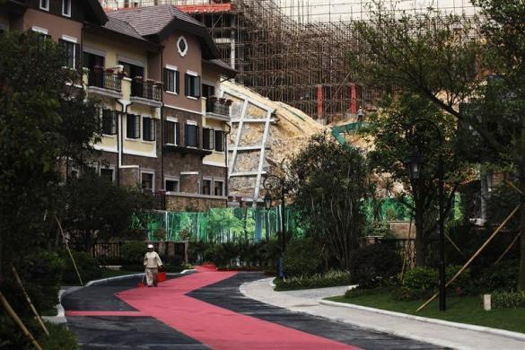 A cleaner walks in front of a house for sale at the replica village of Austria's UNESCO heritage site, Hallstatt, in China's southern city of Huizhou in Guangdong province, June 1, 2012.