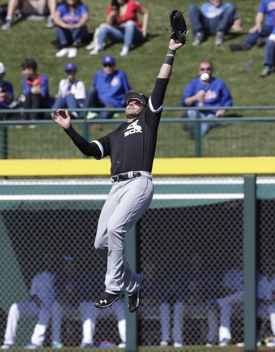 Chicago White Sox left fielder Nicky Delmonico leaps but is unable to catch the double hit by Chicago Cubs' Victor Caratini during the first inning of a spring training baseball game, Tuesday, Feb. 27, 2018, in Mesa, Ariz. (AP Photo/Carlos Osorio)