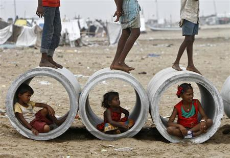 Children sitting inside cement water pipes play on the Marina beach in Chennai October 10, 2013. REUTERS/Babu/Files