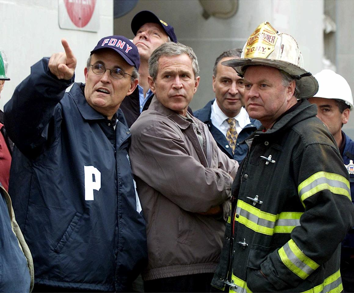 President Bush, center, New York City Mayor Rudolph Giuliani, left, and New York Governor George Pataki, second from left, Sen. Charles Schumer, D-N.Y., second from right, and New York City Fire Commissioner Thomas Van Essen, right, look toward the fallen buildings during a tour of the World Trade Center, Friday, Sept. 14, 2001 in New York. (AP Photo/Doug Mills)