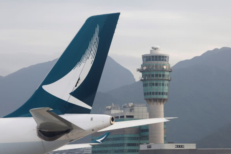 FILE PHOTO: A Cathay Pacific jet is seen in front of air traffic control tower at the Hong Kong International Airport, Hong Kong