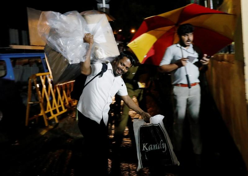 A Sri Lankan election official arrives with a ballot box to a counting center after the voting ended during the presidential election day in Colombo
