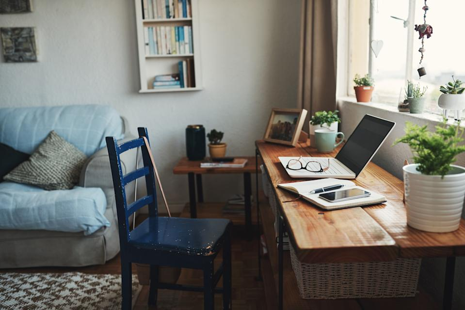 Cropped shot of technology and a notebook on a desk in an empty home office during the day