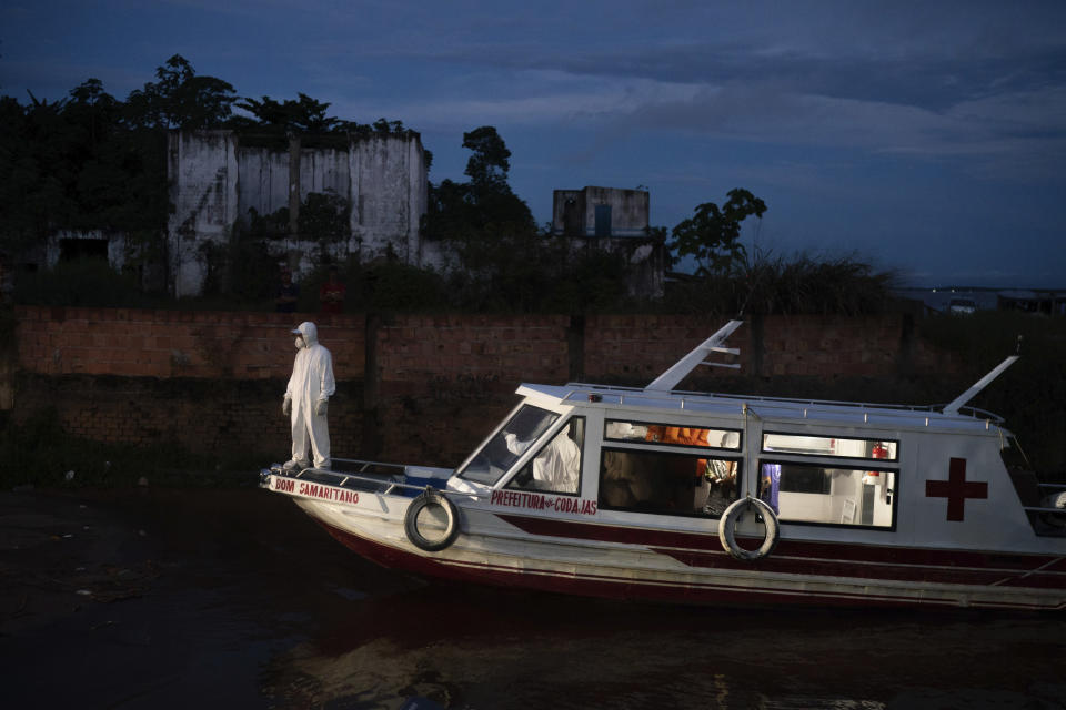 A health worker stands on a boat carrying COVID-19 patient Jose da Conceição as he waits for an ambulance to transfer him to a hospital after arriving in the port of Manacapuru, Amazonas state, Brazil, Monday, June 1, 2020. (AP Photo/Felipe Dana)