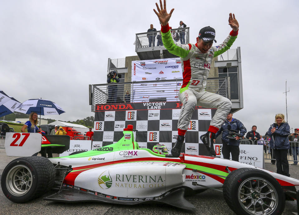 """FILE - In this April 22, 2018 file photo, Mexico's Patricio """"Pato"""" O'Ward celebrates winning the Indy Lights race #2 during the Honda Indy Grand Prix of Alabama at Barber Motorsports Park, in Birmingham, Ala. James Hinchcliffe has been released from the new Arrow McLaren SP Racing team, two people with direct knowledge of the situation told The Associated Press, despite repeated public assurances that the popular Canadian was not leaving the organization once McLaren came aboard. Hinchcliffe learned Sunday he was being replaced by 2018 Indy Lights Champion Pato O'Ward and said his farewells at the team shop Monday, Oct. 28, 2019, the two people said. (AP Photo/Butch Dill, File)"""