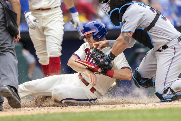 Philadelphia Phillies' J.T. Realmuto is out on attempted steal of home as Miami Marlins catcher Jorge Alfaro (38) makes the tag during the sixth inning of a baseball game Sunday, July 18, 2021, in Philadelphia. (AP Photo/Laurence Kesterson)