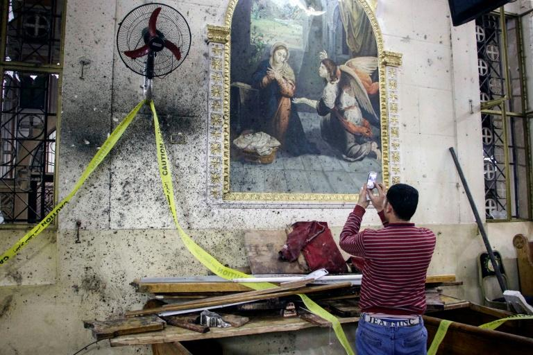 A man photographs the destruction inside a Coptic church in the Egyptian city of Tanta, hit by a bomb on April 9, 2017