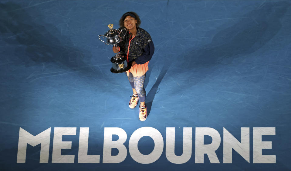 Japan's Naomi Osaka holds the Daphne Akhurst Memorial Cup defeating United States Jennifer Brady in the women's singles final at the Australian Open tennis championship in Melbourne, Australia, Saturday, Feb. 20, 2021.(AP Photo/Hamish Blair)