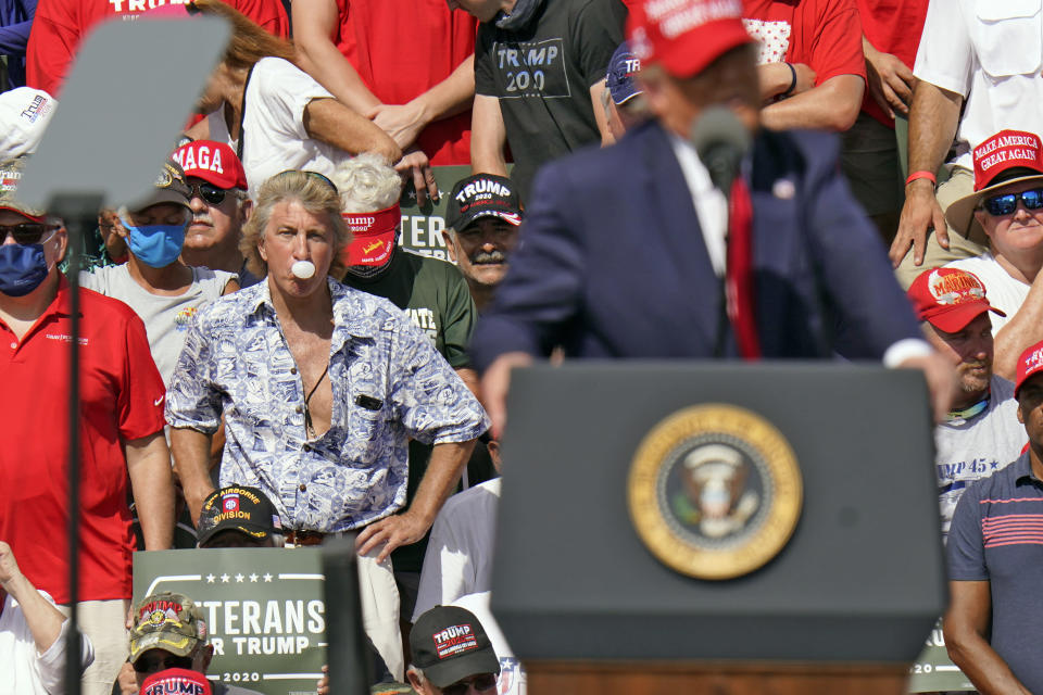 A supporter blows a bubble with gum as President Donald Trump speaks during a campaign rally Thursday, Oct. 29, 2020, in Tampa, Fla. (AP Photo/Chris O'Meara)