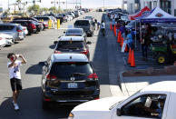 """Voters line up in their cars for a drive-thru """"ballot drop-off parade"""" during the first day of early voting in North Las Vegas Saturday, Oct. 17, 2020. (Steve Marcus/Las Vegas Sun via AP)"""