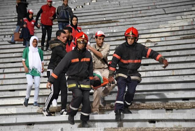 Emergency personnel carry an injured supporter at the Mohammed V Stadium in Casablanca following clashes between rival fans of Raja de Casablanca after their match against Chabab Rif Al Hoceima on March 19, 2016 (AFP Photo/)