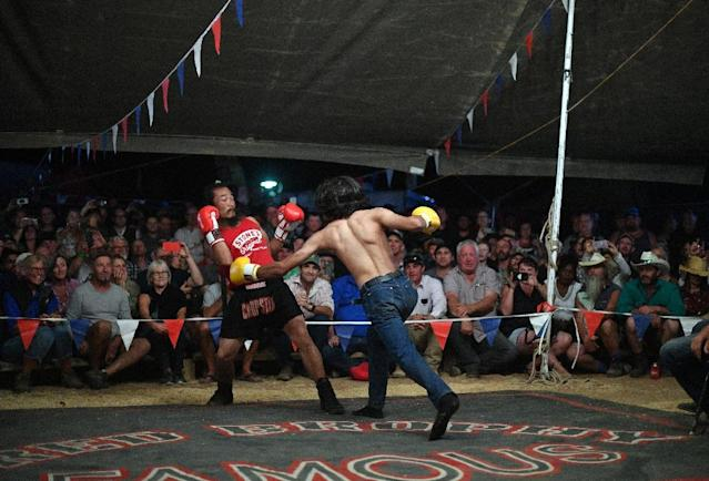 After sundown, many head to a boxing tent, where audience members can challenge the members of a travelling boxing troupe to a fight in front of cheering spectators (AFP Photo/Saeed KHAN)