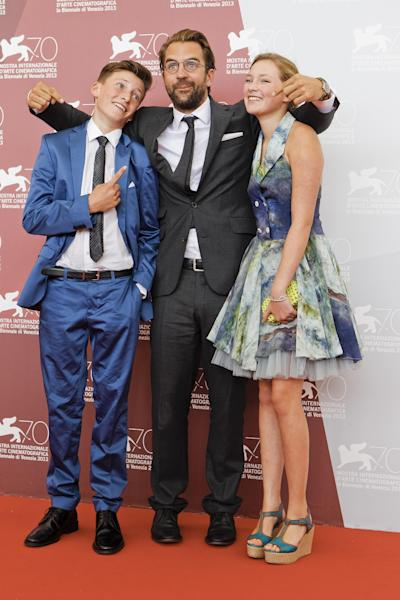 Actors Levin Liam, left, and Helena Phil, right, pose with director Rick Ostermann during the photo call for the movie 'Wolfschildren' at the 70th edition of the Venice Film Festival in Venice, Thursday, Aug. 29, 2013. (AP Photo/Andrew Medichini)