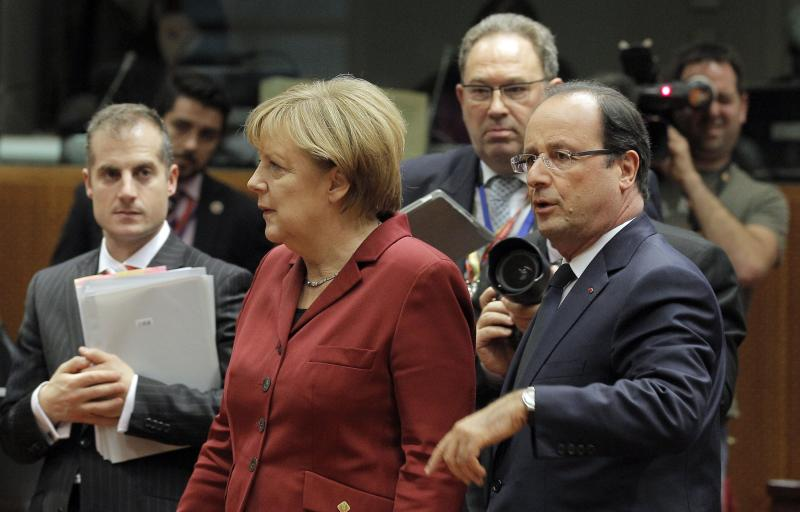 German Chancellor Angela Merkel, second left, and French President Francois Hollande, second right, arrive for a round table meeting at an EU summit in Brussels, Thursday, Oct. 24, 2013. A two-day summit meeting of EU leaders is likely to be diverted from its official agenda, economic recovery and migration, after German Chancellor Angela Merkel complained to U.S. President Barack Obama that U.S. intelligence may have monitored her mobile phone. (AP Photo/Yves Logghe)