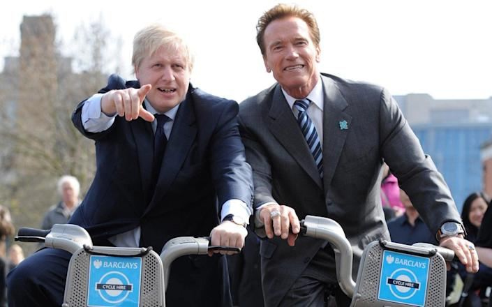 Boris Johnson takes Arnold Schwarzenegger for a ride on one of his 'Boris bikes' during his visit to City Hall in London in 2011 - Stefan Rousseau/PA Wire