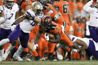 Oregon State running back Deshaun Fenwick (5) is brought down by Washington's Edefuan Ulofoshio, left, and Cameron Williams during the first half of an NCAA college football game Saturday, Oct. 2, 2021, in Corvallis, Ore. (AP Photo/Amanda Loman)