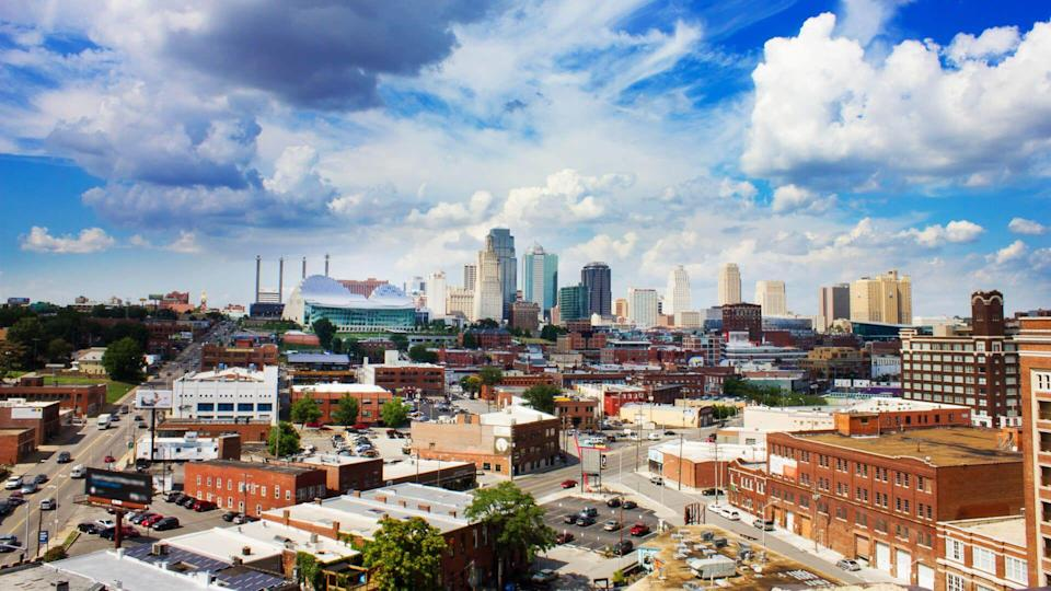 Downtown Kansas City, Missouri at daytime under a big blue sky and striking clouds.