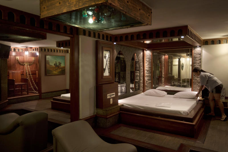 "A hotel worker makes the bed inside the Medieval Room, where chains hang on the wall, reflected in the mirror at left, at the Shalimar Hotel, known as a love hotel in Rio de Janeiro, Brazil, Thursday, Jan. 17, 2013. With the arrival of next year's World Cup soccer tournament and the 2016 Olympic Games to this seaside city, local officials are scrambling to bridge a chronic hotel bed shortage so severe that during a UN conference here last year, the mayor had to appeal to residents to open their apartments to visitors. The plan? Slash property taxes for love hotels, known as ""motels"" in Portuguese, that agree to tone down the decor and free up 90 percent of their rooms for the tsunami of visitors expected to flood the city. (AP Photo/Felipe Dana)"