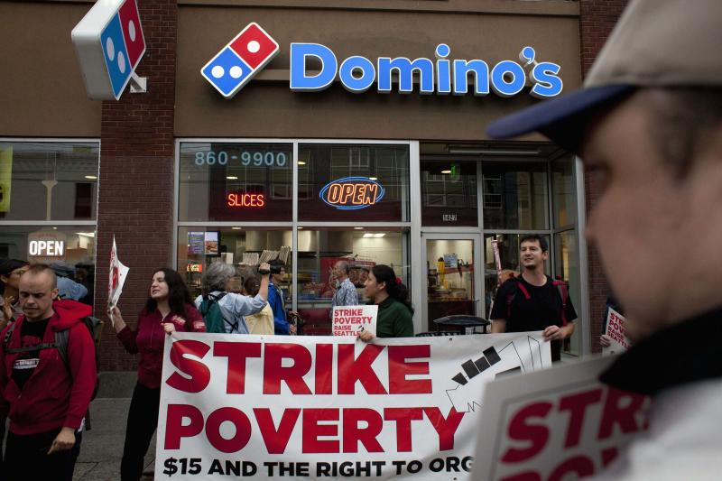 Demonstrators are pictured in front of Domino's Pizza during a strike aimed at the fast-food industry and the minimum wage in Seattle, Washington August 29, 2013. Fast-food workers went on strike and protested outside restaurants in 60 U.S. cities on Thursday, in the largest protest of an almost year-long campaign to raise service sector wages. REUTERS/David Ryder (UNITED STATES - Tags: FOOD CIVIL UNREST BUSINESS EMPLOYMENT)