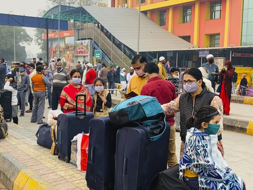 A family wearing face mask as a precaution against coronavirus waits for transport after arriving at railway station in New Delhi, India, Friday, Nov. 6, 2020. A thick quilt of smog lingered over the Indian capital and its suburbs on Friday, fed by smoke from raging agricultural fires that health experts worry could worsen the city's fight against the coronavirus. Air pollution in parts of New Delhi have climbed to levels around nine times what the World Health Organization considers safe, turning grey winter skies into a putrid yellow and shrouding national monuments. (AP Photo/Rajesh Kumar Singh)