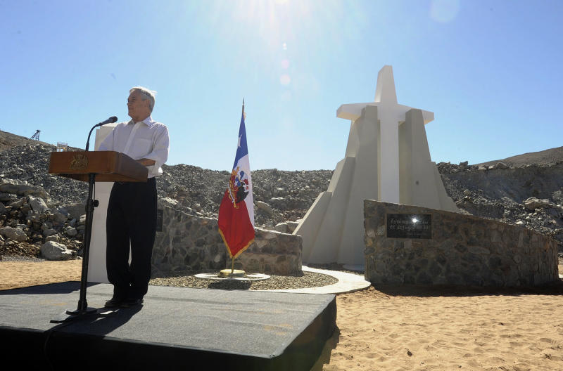 """In this photo released by Chile's Presidency, Chile's President Sebastian Pinera delivers a speech during an event marking the second anniversary of the cave-in at the San Jose mine in the Atacama, honoring the miners who survived in entrapment longer than anyone else before, in front of a monument on the outskirts of Copiapo, Chile, Sunday, Aug. 5, 2012. Pinera traveled to the northern city of Copiapo to join the men at the mouth of the mine that nearly became their rocky grave. They unveiled a five-meter (16 1/2-foot) cross as part of a monument known as the """"The 33 miners of Atacama: The miracle of life."""" (AP Photo/Chile's Presidency)"""