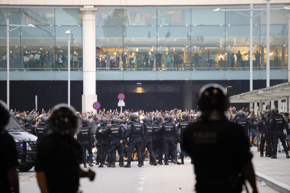 A line of riot police stands in front of protestors outside El Prat airport in Barcelona, Spain, Monday, Oct. 14, 2019. Riot police have charged at protesters outside Barcelona's airport after the Supreme Court sentenced 12 prominent Catalan separatists to lengthy prison terms for their roles in a 2017 push for the wealthy Spanish region's independence. (AP Photo/Emilio Morenatti)