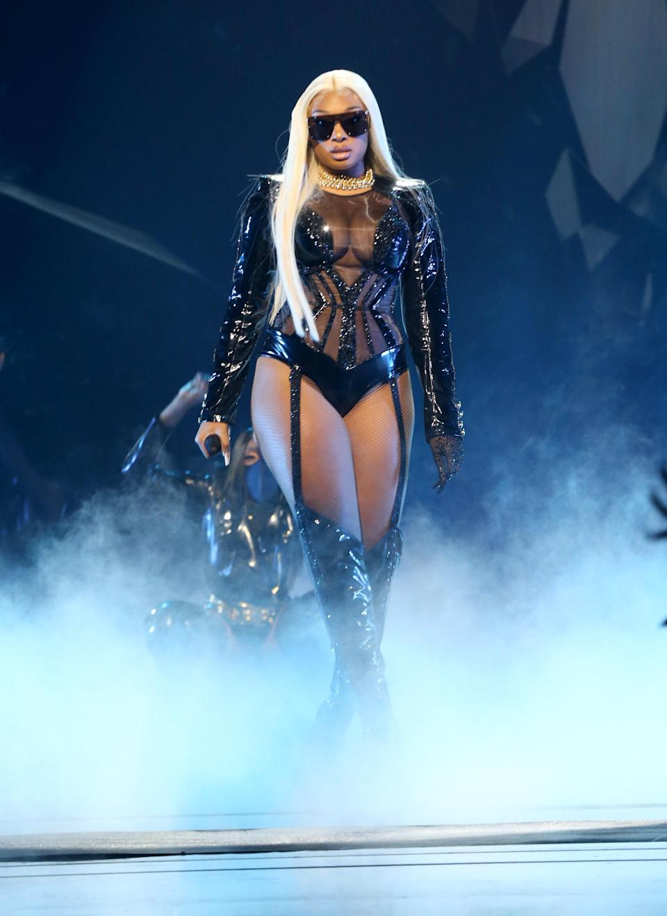 """Megan wasn't lying when she said """"switch my wig, make him feel like he's cheating."""" For her second look of the night, she hit the stage in a blonde wig, sequined leotard, and thigh-high leather boots."""