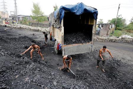 FILE PHOTO: Labourers load coal onto a supply truck on the outskirts of Jammu