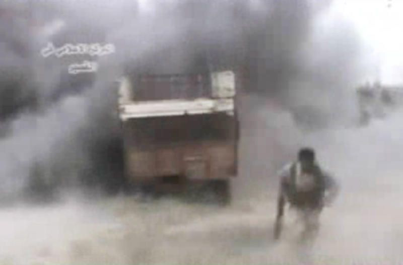FILE - In this Sunday, May 19, 2013 file image from amateur video obtained by a group which calls itself Ugarit News, a rebel runs from an explosion, in Qusair, Syria. The video is consistent with independent AP reporting. Never in history has a war been covered in the way that Syria's civil war has: A constant stream of hundreds of thousands of videos instantaneously bringing all the viciousness, brutality and gore instantaneously and vividly to millions of viewers across the globe via YouTube and social media. The raw footage from Syria's battlefields comes in a perpetual stream _ a vicious civil war brought instantaneously to millions of viewers across the globe via YouTube and social media.(AP Photo)