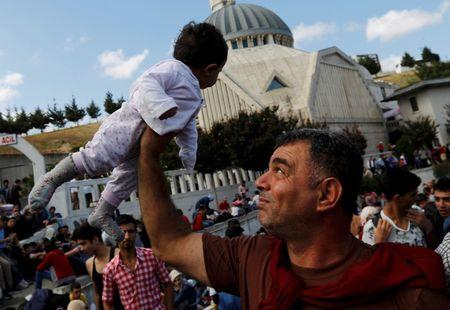 Syrian Kurd Salah ad-Din lifts his 7-month-old daughter Hiro Belo as they wait at the main bus station in Istanbul, Turkey, September 15, 2015.  REUTERS/Murad Sezer