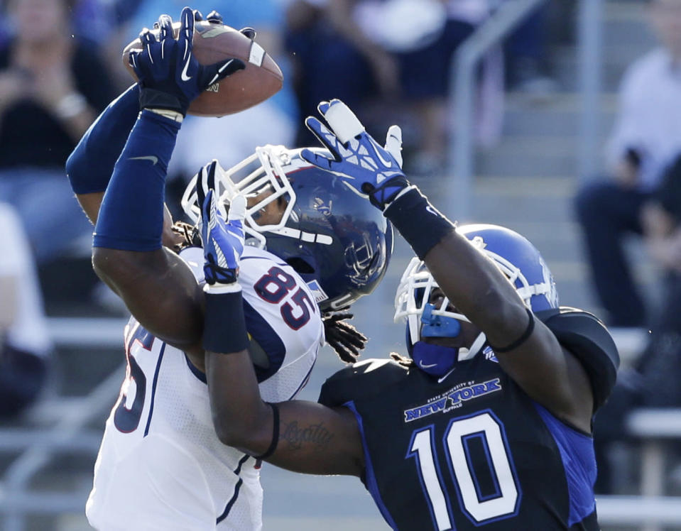 Connecticut wide receiver Geremy Davis (85) makes a catch in front of Buffalo defensive back Witney Sherry (10) during the first half of an NCAA college football game on Saturday, Sept. 28, 2013, in Buffalo, N.Y. (AP Photo/Mike Groll)