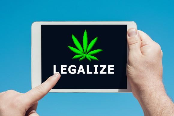 A person holding a tablet and touching the screen with shows a cannabis leaf and says the word Legalize.