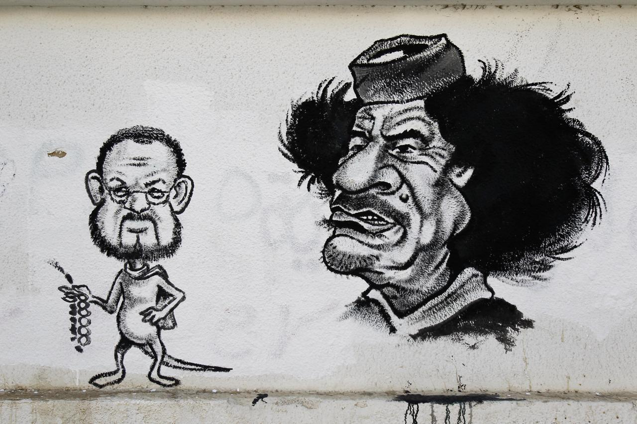 A graffiti depicting Libya's ousted Moammar Gadhafi, right, and his public relations officer Youssef Shakhir with a rat's tail and holding prayer beads, seen on a street in Tripoli, Libya, Tuesday, Sept. 20, 2011. Libyan graffiti artists are taking advantage of newfound freedom to make fun of ousted leader Moammar Gadhafi on the streets of Tripoli, after 42-years of authoritarian rule artists feel able to express themselves in public spaces. (AP Photo/Francois Mori)