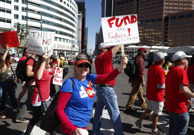 <p>Keli Kinsella, a teacher in the Cherry Creek school district, waves a sign as teachers march during a rally, Friday, April 27, 2018, in Denver, Colo. (Photo: David Zalubowski/AP) </p>