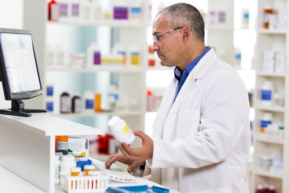 Pharmacist at counter holding pill bottle