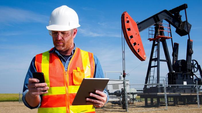 A royalty free image from the oil and gas industry of an engineer in front of a pumpjack drilling for natural gas and other resources.